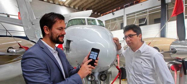 Paweł Malicki (po lewej) prezentuje działanie aplikacji do zamawiania helikopterów